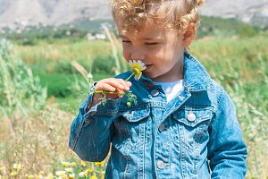 kid smelling a flower in countryside