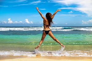 Summer scene with beautiful young woman enjoying the beach and jumping near sea in Bali.