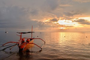 Tropical island sunset with traditional Bali boat on sea with beautiful sun reflection in water