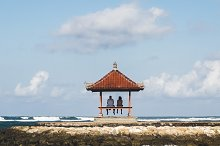 Loving couple seating in pavilion and enjoying a sea view. Romantic arbor with a red roof on a seaside.