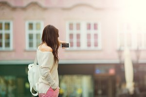 Young woman taking self portrait in european city. Caucasian tourist enjoy her european summer vacation in Prague