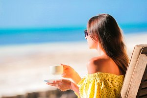 Young woman drinking hot coffee enjoying beach view. Beautiful woman relax during exotic vacation on the beach enjoying sweet coffee