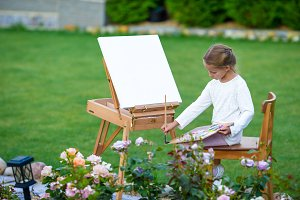 Adorable little girl painting a picture on easel outdoors. Little artist keen on her hobby.