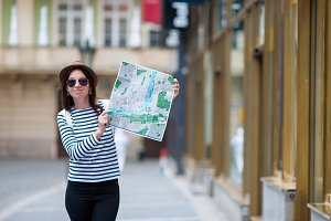 Happy young woman with a city map in Europe. Travel tourist woman with map outdoors during european holidays