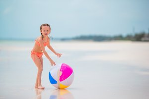 Little girl playing with air ball on white beach