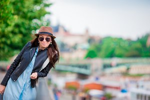 Happy young urban woman in european city. Caucasian tourist walking along the deserted streets of Europe. Warm summer early morning in Prague, Czech Republic