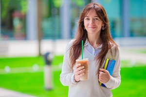 Happy young student girl with a coffee-to-go, walking in a summer park and holding books for reading.