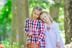 Spring garden, spring flowers, adorable little girls and tulips. Cute kids with a basket in blooming garden on warm day