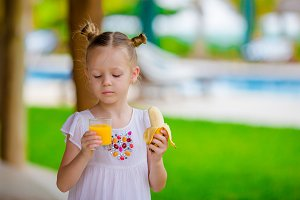 Adorable little girl with juice and banana at outdoor cafe. Fresh food and fruits in exotic country