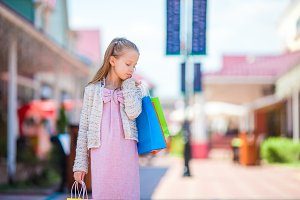 Portrait of little girl shopping outdoors