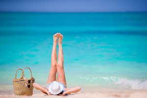 Young beautiful girl relaxing on white beach. Tourist woman enjoy beach vacation lying on the sand