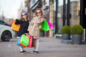 Adorable little girls with bags on shopping outdoors