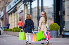 Little fashion girl with shopping bags outdoors in big city