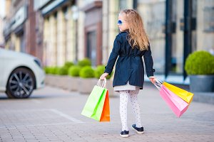 Adorable little girl having fun with shopping bags outdoors