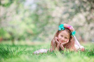 Portrait of adorable little girl in blooming cherry tree garden outdoors