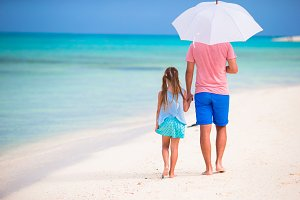 Father and kid walking on white sandy beach
