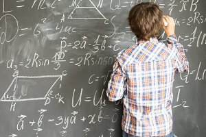 Boy writting on black board