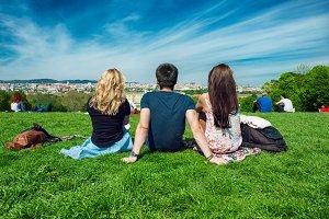 friends sitting on green grass