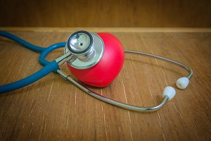 Red heart and stethoscope on wooden