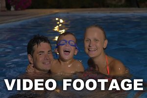 Happy family with child in the pool