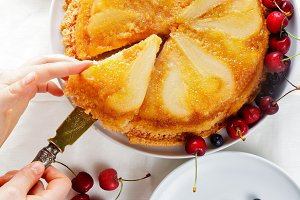 cutting Upside-Down cake with pears.