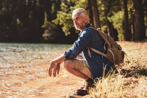 Mature man sitting next to a lake
