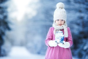 Adorable little girl with flashlight and candle in winter on Christmas outdoors