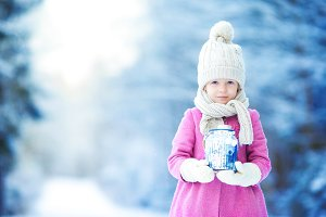 Little girl with flashlight and candle in winter day outdoors