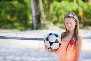Little adorable girl playing voleyball on beach with ball
