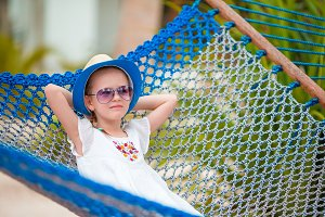 Adorable little girl on summer vacation relaxing in hammock
