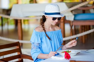 Young woman having breakfast at outdoor cafe on summer vacation
