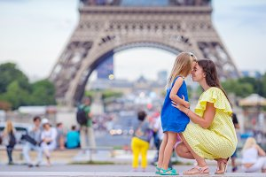 Happy mother and little adorable girl in Paris near Eiffel Tower during summer french vacation