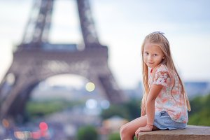Cute little girl background the Eiffel tower during summer vacation in Paris