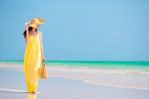 Young beautiful woman in big hat during tropical beach vacation