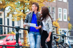 Happy couple sightseeing city with map in Europe