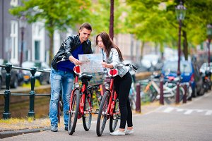 Young tourists couple looking at map with bikes in european city