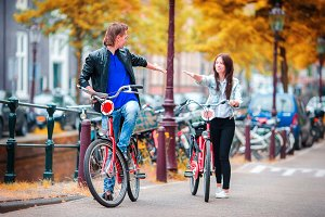 Young happy caucasian couple on bikes in Amsterdam