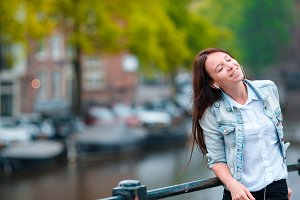 Young beautiful woman listening to music background of canal in Amsterdam, Netherlands