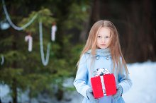 Adorable little girl with christmas box gift in winter outdoors