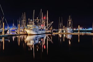 Boats in harbor lit up at night