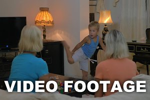 Boy dancing for grandmothers at home