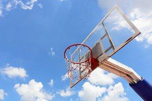 Basketball hoop with a blue sky.
