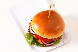 Delicious fresh homemade burger with spicy tomato sauce and beef over light background.  Top view