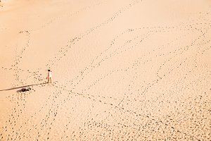 Woman walking on sandy beach in sunset leaving footprints in the sand. Beach, travel, concept. Copy space.
