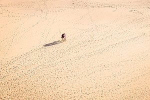 Woman and man walking on sandy beach in sunset leaving footprints in the sand. Beach, travel, concept. Copy space.
