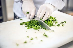 Cook's hands cutting parsley