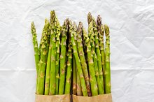 Asparagus in paper bag on white