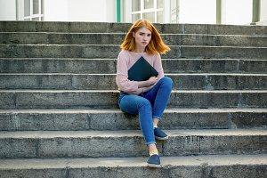 Red-haired girl sitting on the stair