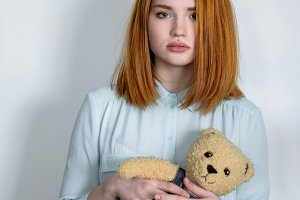Girl standing with a teddy bear