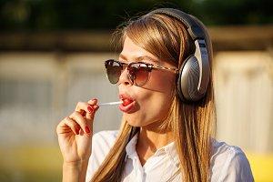Girl licking lollipop. Music